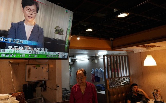 Customers watch Hong Kong Chief Executive Carrie Lam make an announcement on TV in Hong Kong, on Wednesday, Sept. 4, 2019. (AP Photo)
