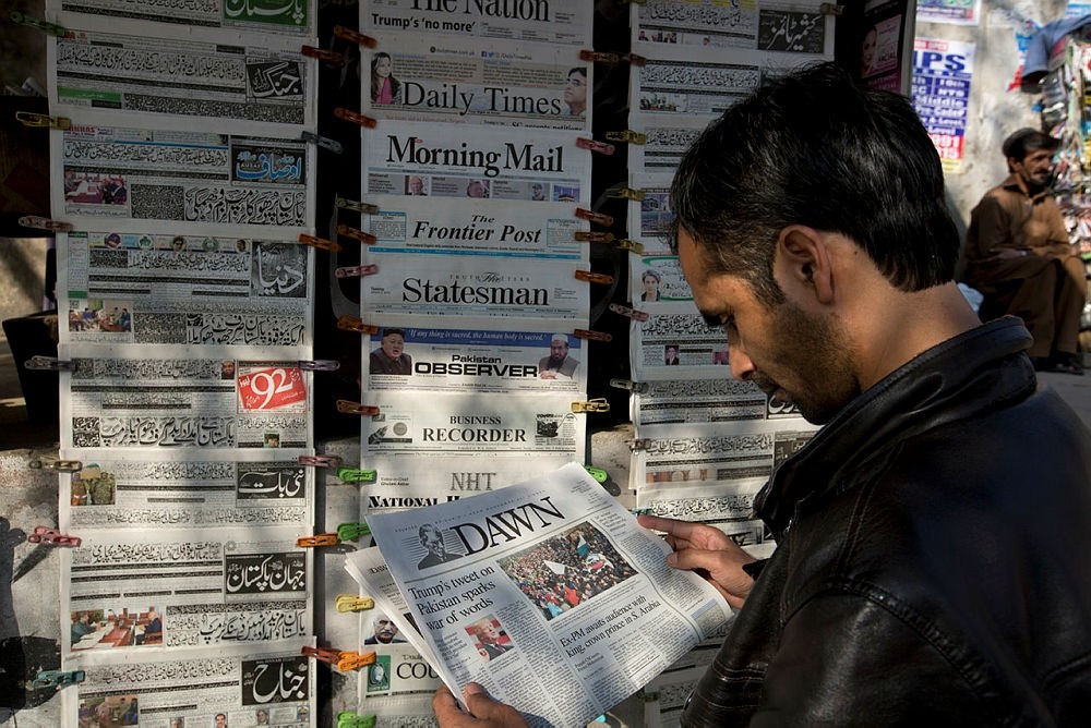 A man reads a local newspaper carrying news about a tweet by U.S. President Donald Trump at a newsstand in Islamabad, Pakistan, Tuesday, Jan. 2, 2018. (AP Photo)