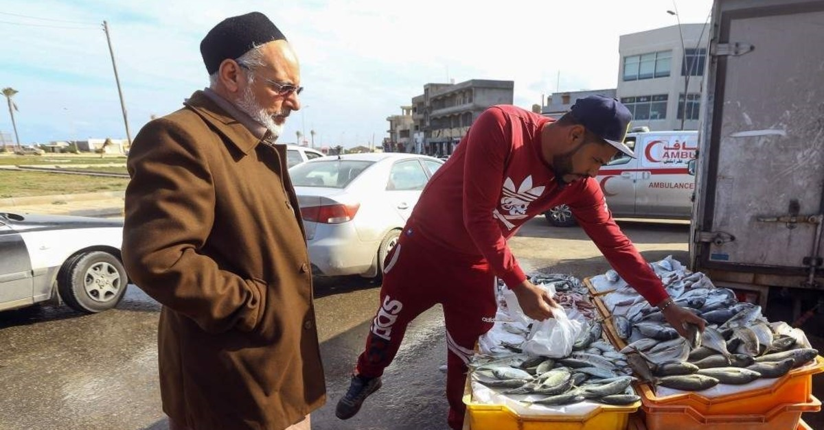 A man buys fresh fish from a stall in the Libyan capital Tripoli, Jan.13, 2020. (AFP PHOTO)