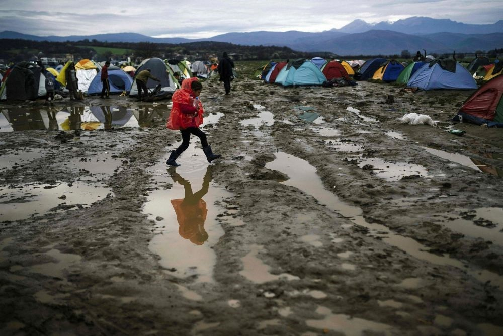 A girl walks in the mud in a makeshift camp at the Greek-Macedonian border, near the Greek village of Idomeni, where thousands of refugees and migrants are stranded by the Balkan border blockade.