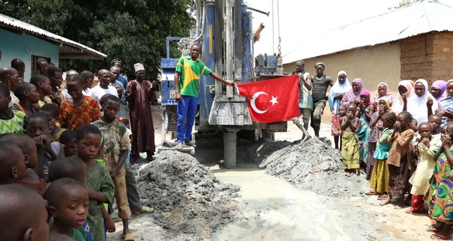 People look on as a water well is drilled in Nigeria's Kwali by a Turkish charity, June 10, 2019.