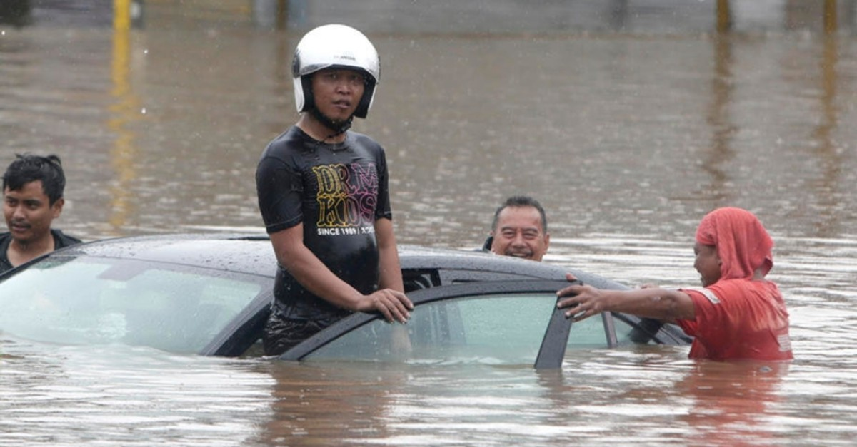 Residents push a submerged car on a flooded street in Jakarta, Indonesia, 01 January 2020. Overnight heavy rains triggered widespread flooding in Jakarta and surrounding areas, bringing traffic to a standstill.  (EPA-EFE Photo)