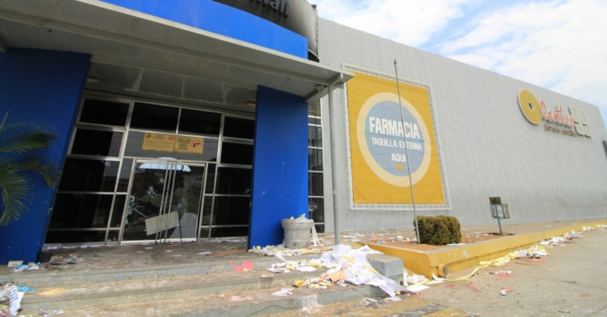 The main entrance of a mall stands burned and damaged after looting the previous day in Maracaibo, Venezuela, Wednesday, March 13, 2019. (AP Photo)