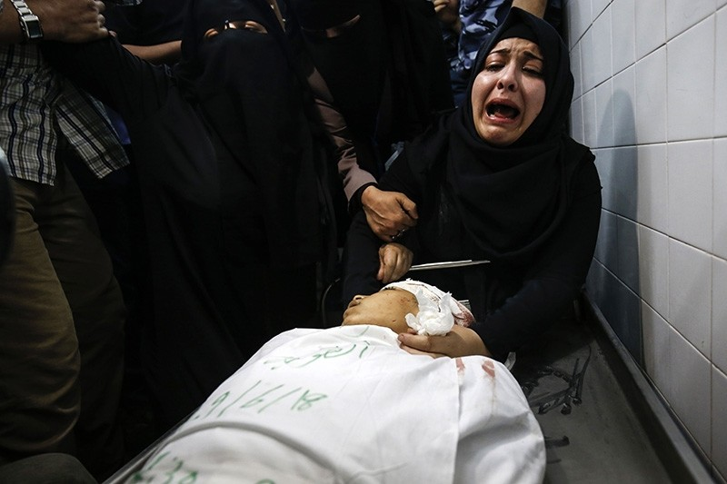 The mother of Yasser Abu al-Naja, a 13-year-old Palestinian boy who was killed in border clashes near Khan Yunis, reacts at a hospital morgue in the Gaza Strip on June 29, 2018. (AFP Photo)