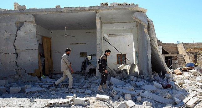 Civil defense members inspect the damage at a site hit by airstrikes on Tuesday, in the town of Khan Sheikhoun (Reuters Photo)