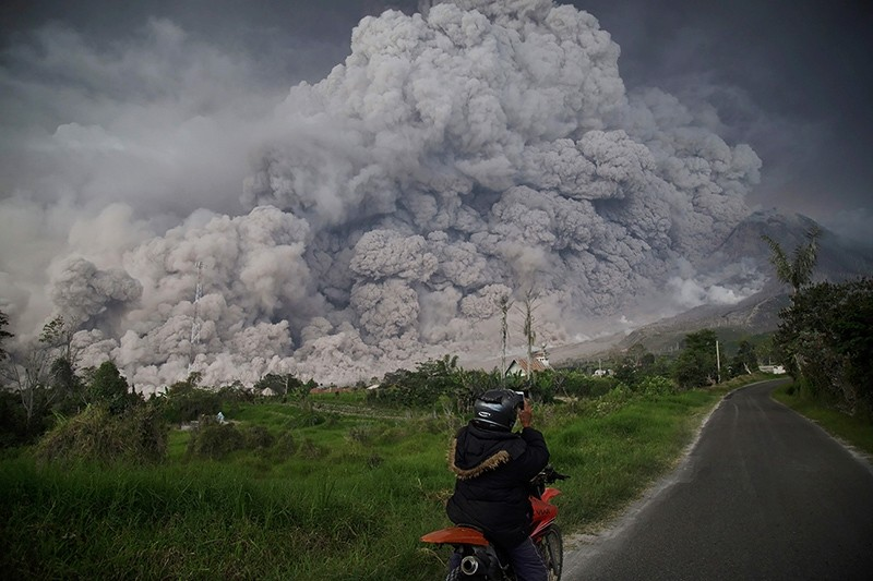A man takes picture of Mount Sinabung volcano as it spews thick volcanic ash into the air in Karo, North Sumatra, Indonesia, Feb. 19, 2018. (AFP Photo)