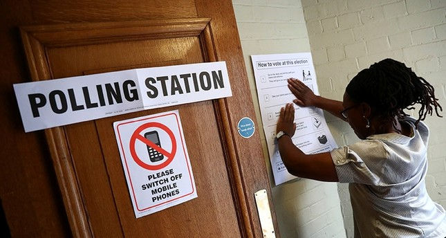 A worker prepares signs outside their polling station on general election day in London, Britain, June 8, 2017 (Reuters Photo)
