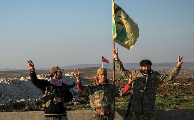 YPG terrorists make a V-sign next to a drawing of imprisoned PKK leader Abdullah Öcalan in Aleppo in February 2015.