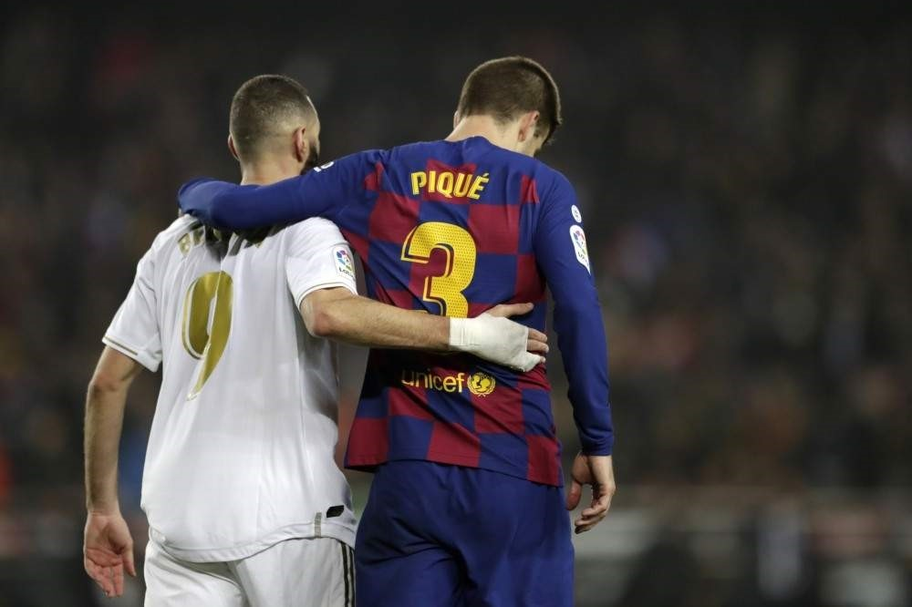 Real Madrid's Karim Benzema and Barcelona's Gerard Pique walk together on the pitch during the match, Dec. 18, 2019. (AP Photo)