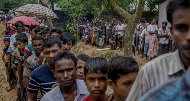 Newly arrived Rohingya wait for their turn to collect shelter building material, distributed by aid agencies in the Kutupalong refugee camp, Bangladesh, Sept. 13.