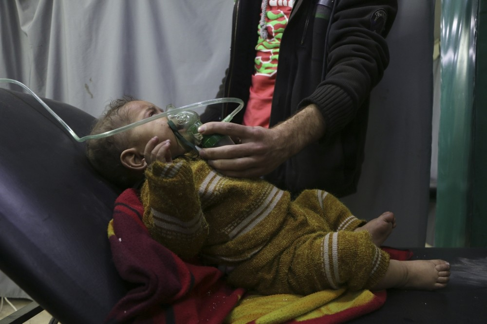 A man gives oxygen through a respirator to a child affected by the chemical attack in Douma.