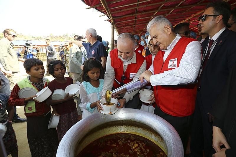 PM Binali Yu0131ldu0131ru0131m (R) and Turkish Red Crescent President Kerem Ku0131nu0131k distribute food to children at the Turkish Cooperation and Coordination Agency (TIKA) food center in Mainnaghota Refugee Camp, southern Bangladesh, Dec. 20, 2017. (AA Photo)