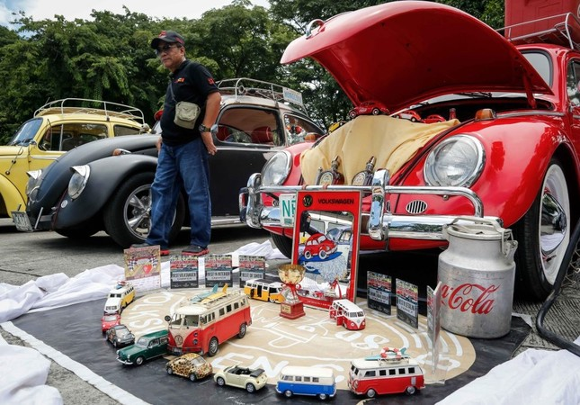 A man walks along different Volkswagen Beetles and collectible toys during the World Volkswagen Day in Quezon city, east of Manila, Philippines.