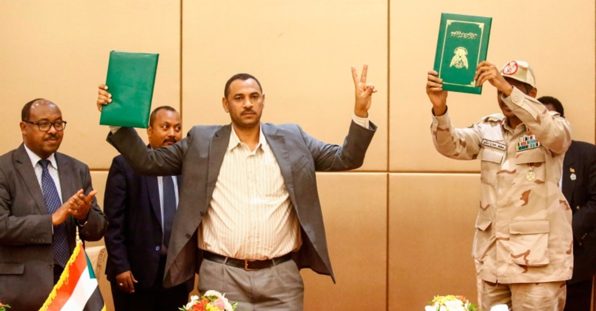 Protest leader Ahmad Rabie, second left, and General Mohamed Hamdan Daglo, Sudan's deputy head of the Transitional Military Council, right, celebrate after signing a constitutional declaration in Khartoum, Sudan, Aug. 4, 2019. (AFP Photo)