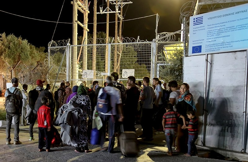 Refugees and migrants stand at the closed gate of the Moria migrant camp, after a fire at the facility, on the island of Lesbos, Greece, Sept. 19, 2016. (Reuters Photo)