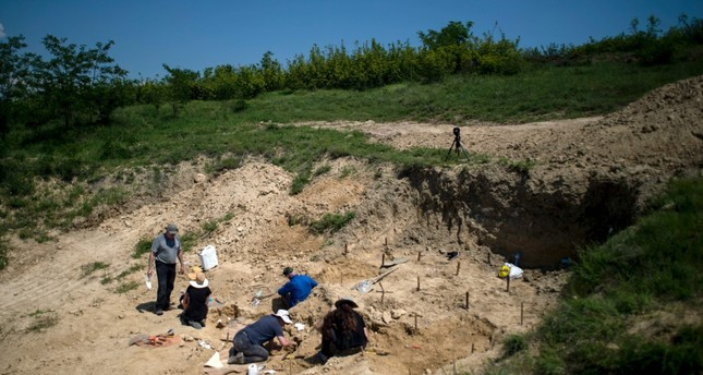 Paleontologists work near the site where a fossilised tooth with three roots was found in 2002, near the village of Rupkite.