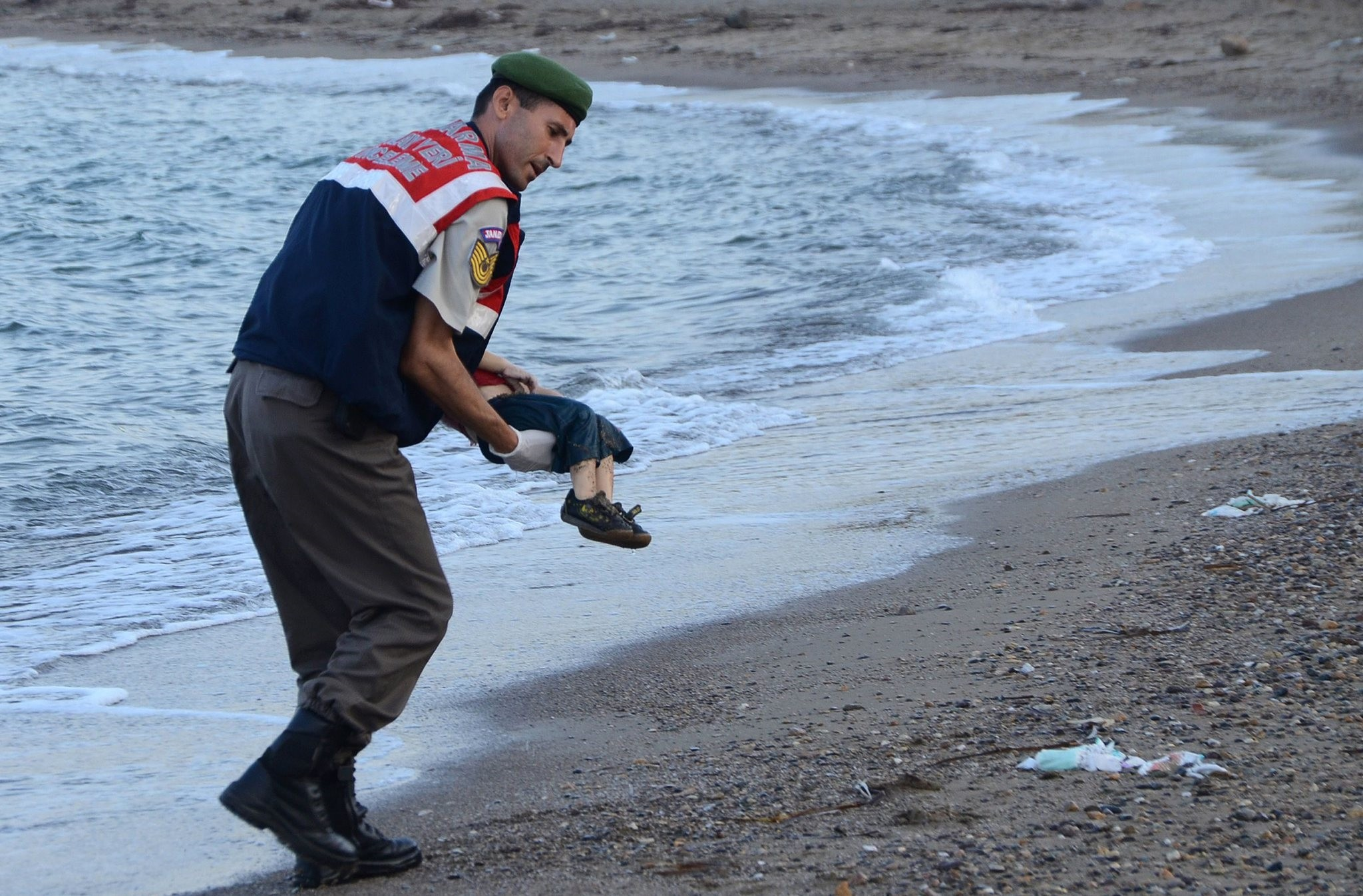 A gendarme  officer carries the dead body of Alan Kurdi on Sept.2, 2015.