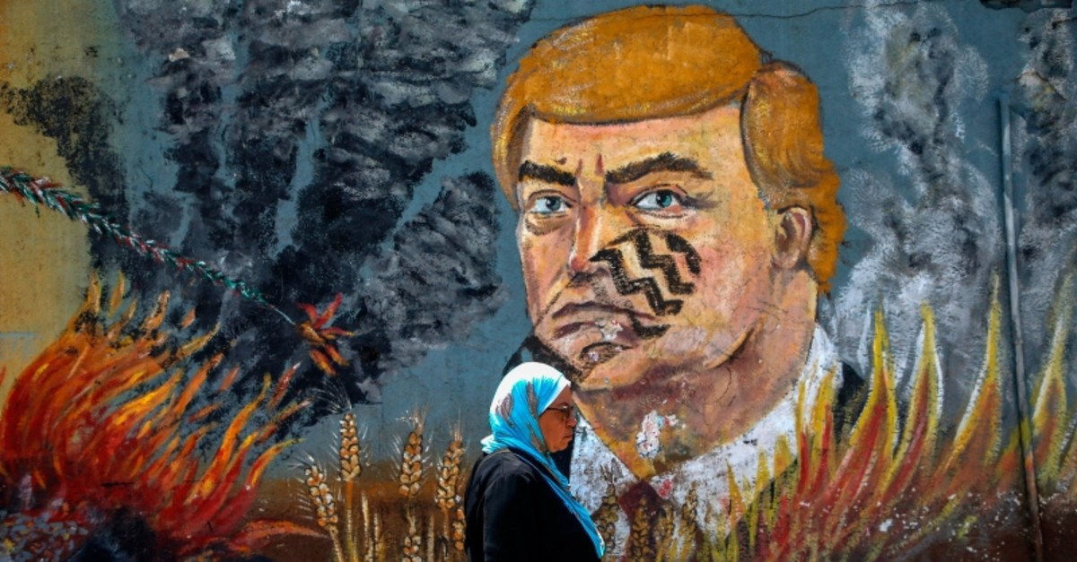 A Palestinian woman walks past a graffiti depicting U.S. President Donald Trump with a footprint on his face in Gaza City on June 23, 2019. (AFP Photo)
