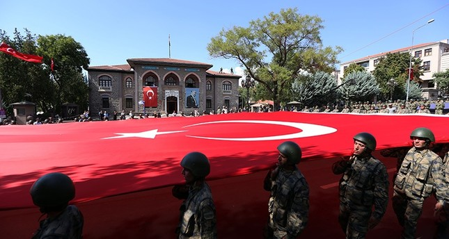 Soldiers carrying a large Turkish flag pass in front of the old (Second) Parliament building, which served between 1924-60, located in Ulus neighborhood of capital Ankara. (AA Photo)