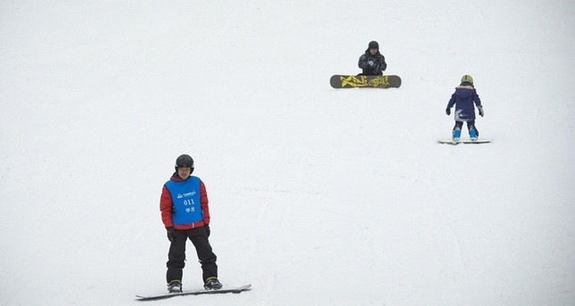 People snowboard at the Wanda Harbin Ice and Snow Park in Harbin.