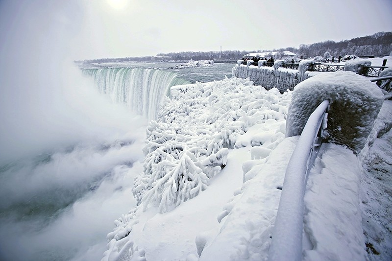 Visitors take photographs at the brink of the Horseshoe Falls in Niagara Falls, Ontario, as cold weather continues through much of the province on Friday, Dec. 29, 2017.