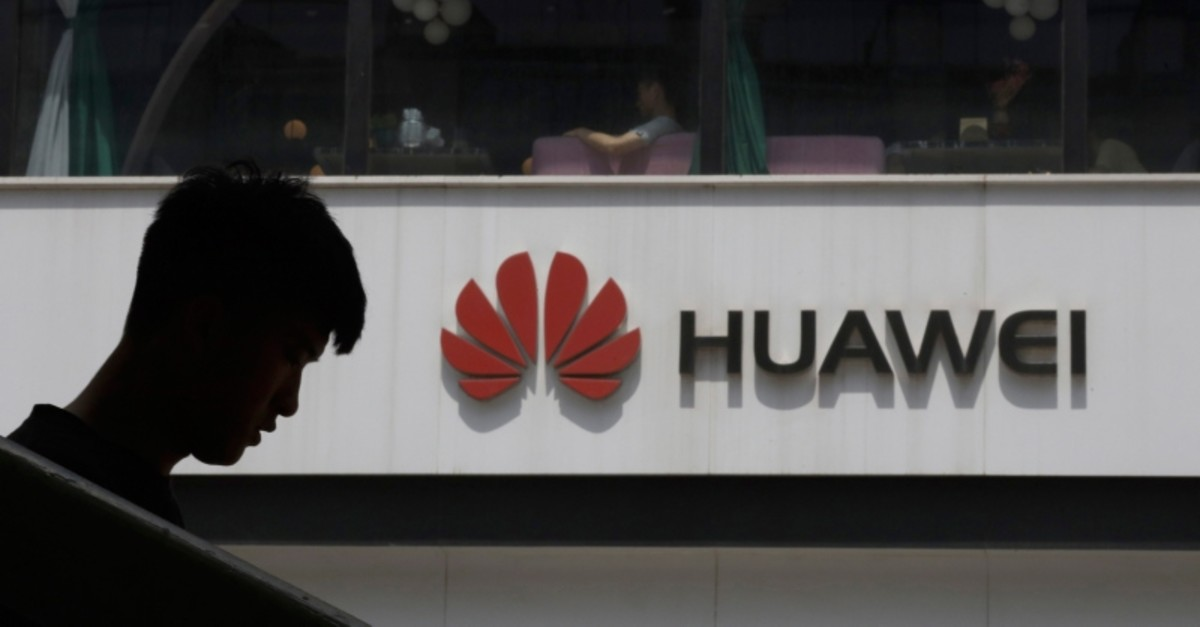 A Chinese man is silhouetted near the Huawei logo in Beijing on Thursday, May 16, 2019. (AP Photo)