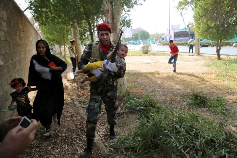 In this Saturday, Sept. 22, 2018 file photo provided by Mehr News Agency, an Iranian soldier carries a child away from a shooting during a military parade, in the southwestern city of Ahvaz, Iran. (AP Photo)