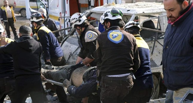 This photo provided by the Syrian Civil Defense White Helmets, which has been authenticated based on its contents and other AP reporting, shows members of the Syrian Civil Defense transporting an injured person after an airstrike hit the northern town of Maaret al-Numan, in Idlib province, Syria, Monday, Dec. 2, 2019. Syrian Civil Defense White Helmets via AP