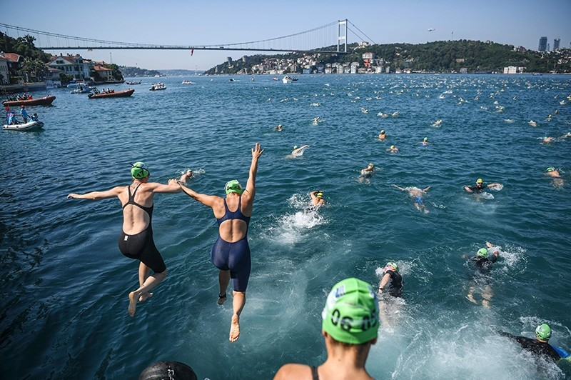 Swimmers jump in the Bosporus river as they take part in the Bosporus Cross-Continental Swim event on July 23, 2017. (AFP Photo)