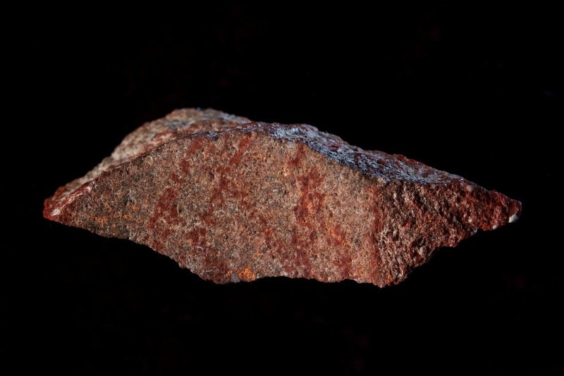 This undated photo provided by Craig Foster in September 2018 shows a drawing made with ochre pigment on silcrete stone, found in the Blombos Cave east of Cape Town, South Africa. (AP Photo)