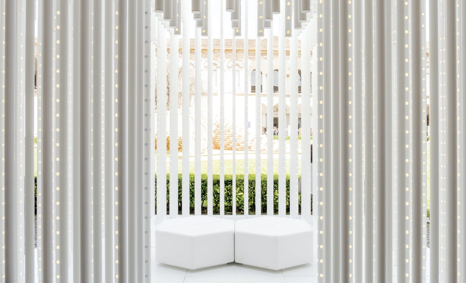 The installation is shaped by the construction of a cubic form, representing the concept of home in its simplest form by using a series of white panels.