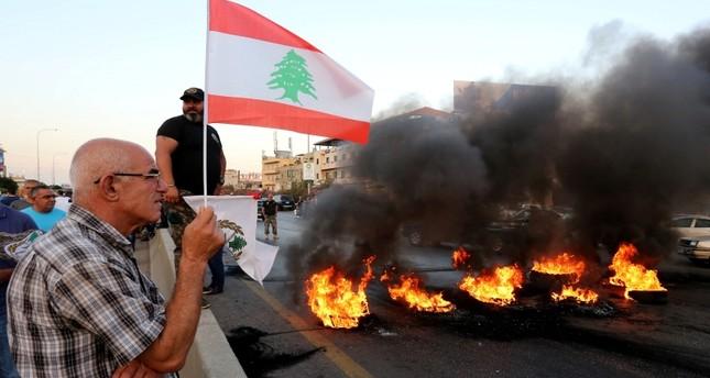 المحتجون أضرموا النار في إطارات سيارات وسدوا طرقا رئيسية تؤدي إلى العاصمة بيروت (رويترز)
