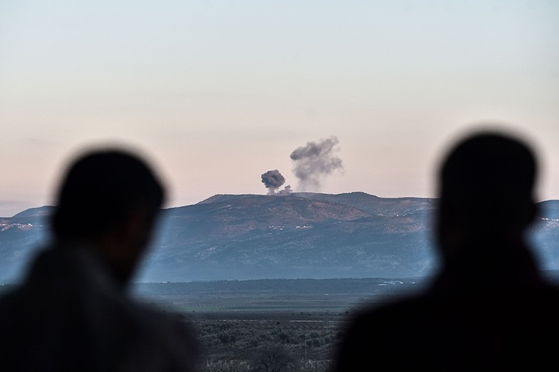 People look on as smoke rises on the Syrian side of the border in Hassa, near Hatay, southern Turkey, as Turkish jet fighters hit terrorist PKK-linked YPG positions (AFP Photo)