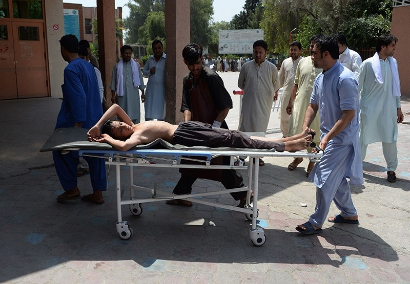Afghan volunteers carry an injured youth on a stretcher to a hospital following an attack that targeted an education department compound in Jalalabad on July 11, 2018. (AFP Photo)