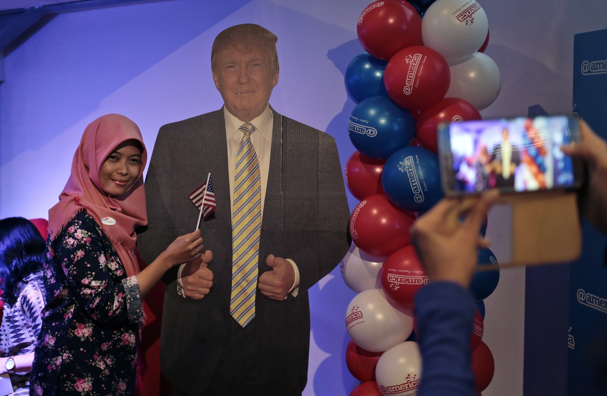 A Muslim woman has her photo taken with the cutout of Trump during an election watch event at U.S. embassy's cultural center