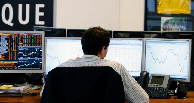A trader checks his screens at investment bank Saxo Banque in Paris. European stocks rallied and the pound hit its highest level on Thursday as markets expected the Remain camp to come out on top in Britain's referendum on EU membership.