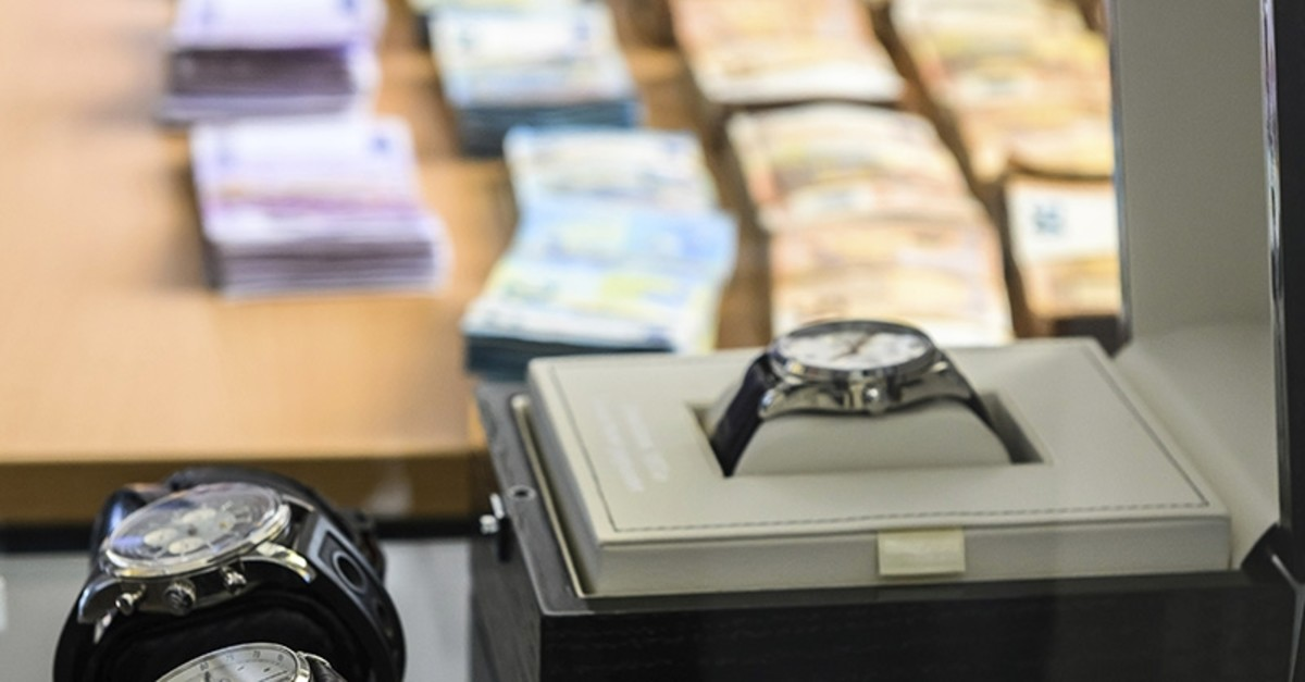 Pieces of evidence like banknotes and luxury watches are presented on Friday, May 3, 2019 at a press conference in Wiesbaden, Germany (AP Photo)