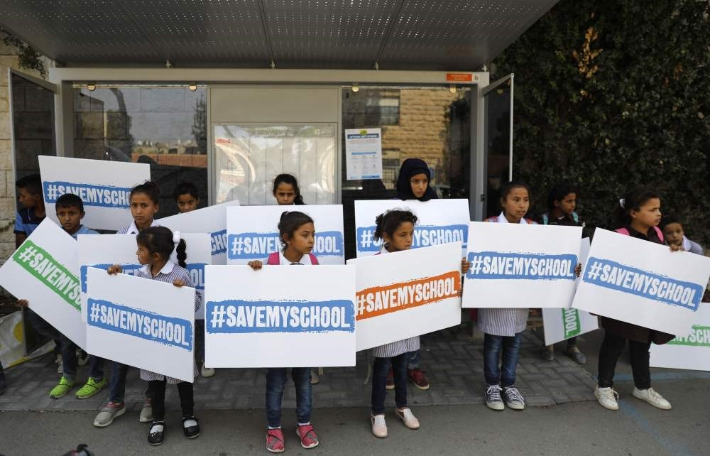 Children from the West Bank Bedouin village of Khan Al Ahmar hold signs with the slogan ,Save my school,, Oct. 4.