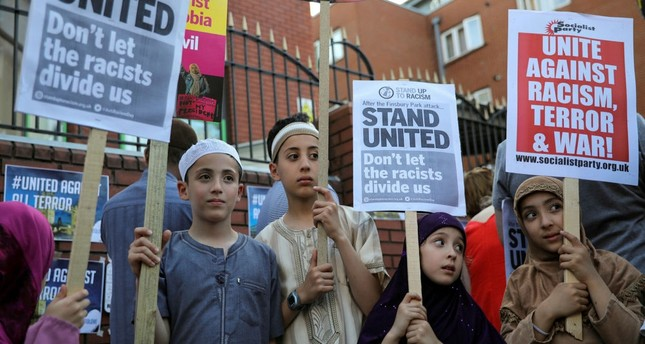 Children hold placards during a vigil near to where a van was driven at Muslims in Finsbury Park, North London, Britain, June 20.