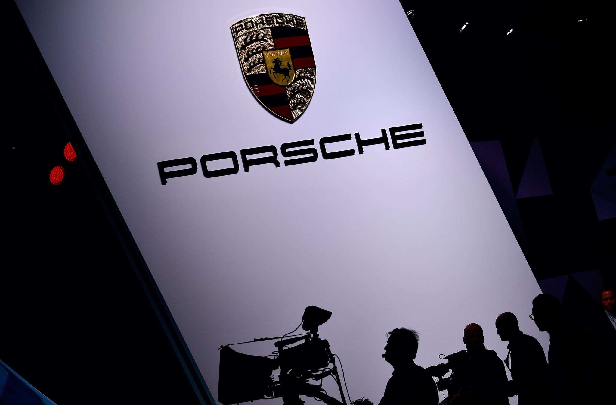 This file photo taken on September 12, 2017 shows cameramen silhouette against an illuminated Porsche ad at the Internationale Automobil Ausstellung (IAA) auto show in Frankfurt am Main. (AFP Photo)