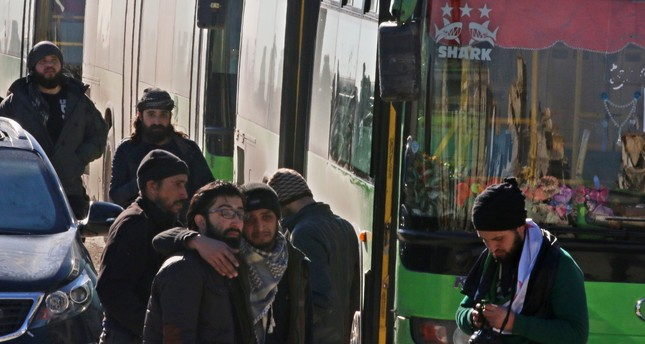 Men react as they stand outside buses evacuating people from a opposition-held sector of eastern Aleppo, Syria December 15, 2016. (REUTERS Photo)