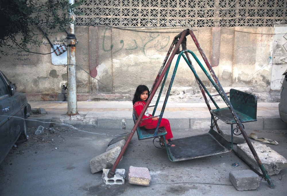A Syrian girl sits on a swing in eastern Damascus on the first day of the Eid al-Fu0131tr holiday, which marks the end of the Muslim holy fasting month of Ramadan, July 6, 2016.