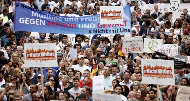 "Participants carry a banner reading ""Muslims and Friends against Terror and Violence"" as they take part ""The Not With Us"" rally against the rising anti-Islam sentiment and extremism in Cologne, Germany, June 17."