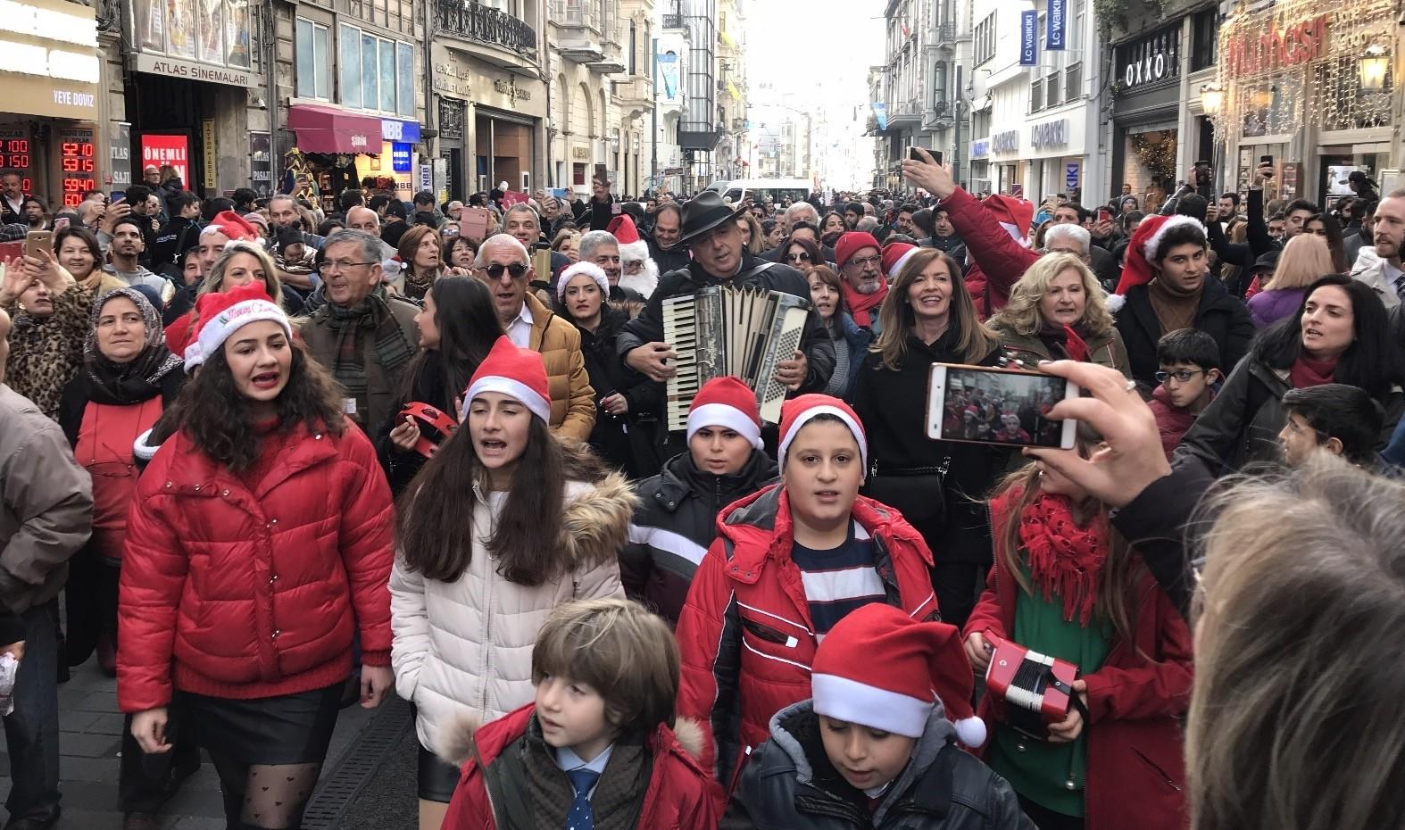 Children and adults sing carols on u0130stiklal Avenue.