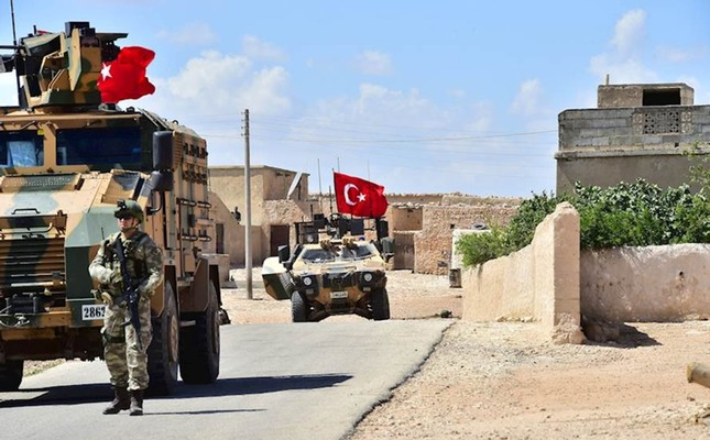 A handout picture released by the Turkish Armed Forces shows Turkish soldiers accompanied by armored vehicles patrolling between the town of Manbij in northern Syria and an area it controls after a 2016 military incursion on June 18, 2018.