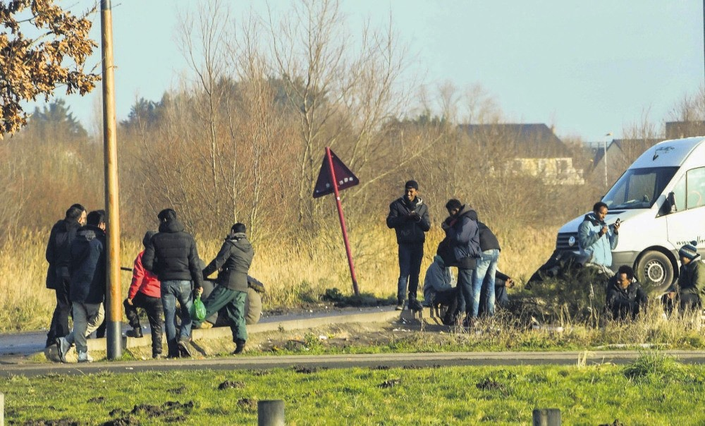 Migrants gather near a truck parking lot close to the N216 highway that leads to the ferry terminal, Calais, Jan. 12.