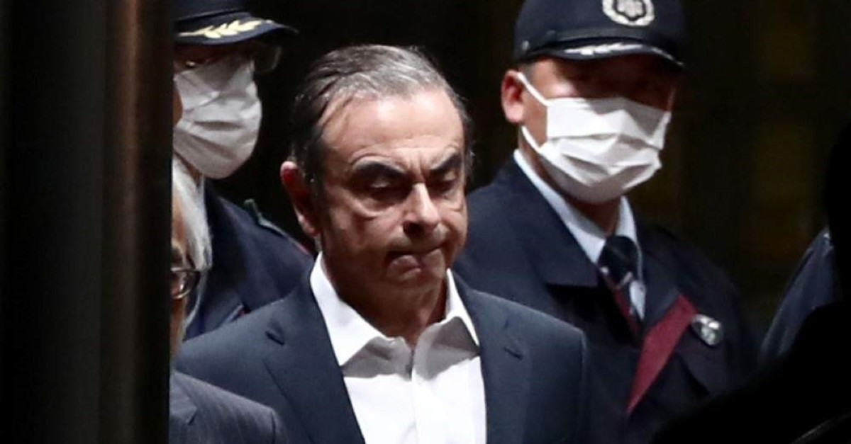 In this file photo taken on April 25, 2019, former Nissan chairman Carlos Ghosn (C) is escorted as he walks out of the Tokyo Detention House following his release on bail in Tokyo. (AFP Photo)