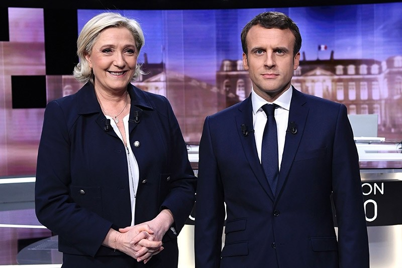 French presidential election candidate for the far-right Front National (FN) party, Marine Le Pen (L) and candidate for the En Marche ! movement, Emmanuel Macron pose before a live brodcast in Paris on May 3, 2017. (AFP Photo)
