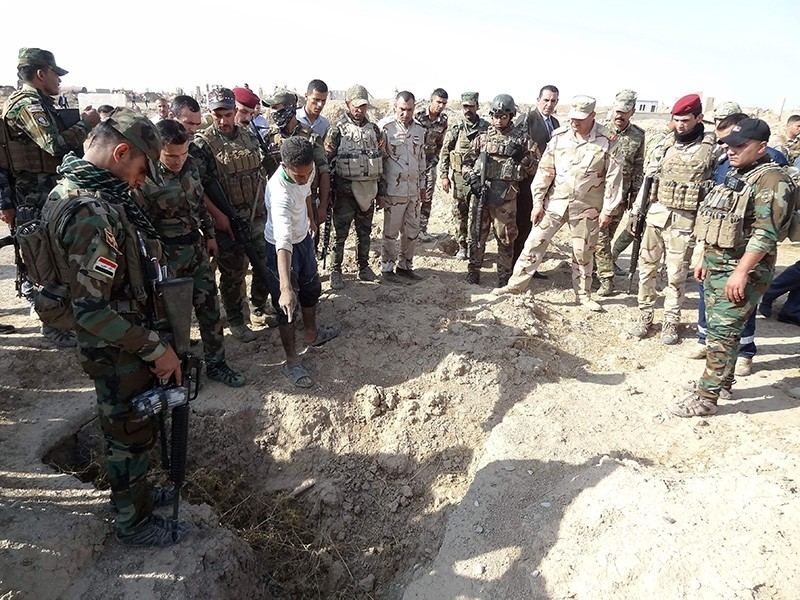Iraqi forces search the site of a suspected mass grave containing the remains of victims of the Islamic State group, near the former al bakara military base on November 11, 2017, south west of Hawija. (AFP Photo)