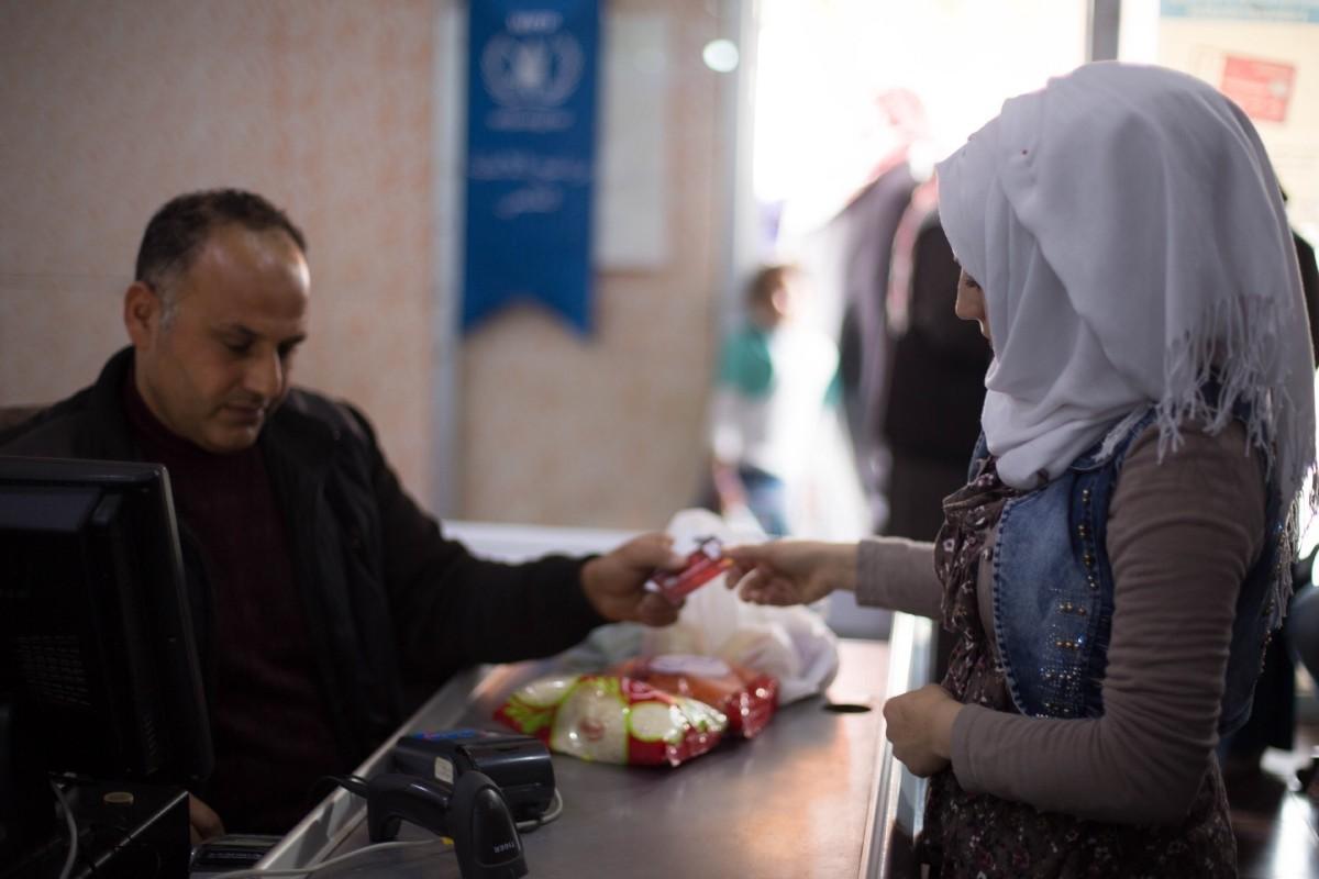 Nour, a Syrian refugee living in Aku00e7akale, u015eanlu0131urfa, hands her Ku0131zu0131lay Card to the cashier after shopping for groceries.